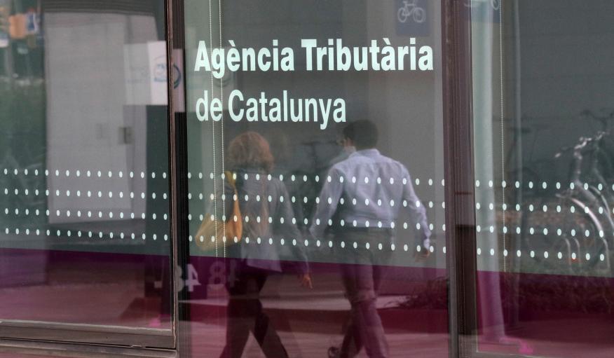 2 personas pasan ante la sede de la Agència Tributària de Catalunya en Barcelona