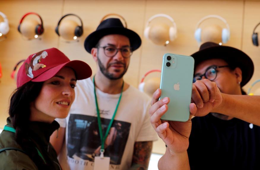 Usuarios de Apple en una de sus tiendas observando en funcionamiento de un iPhone.