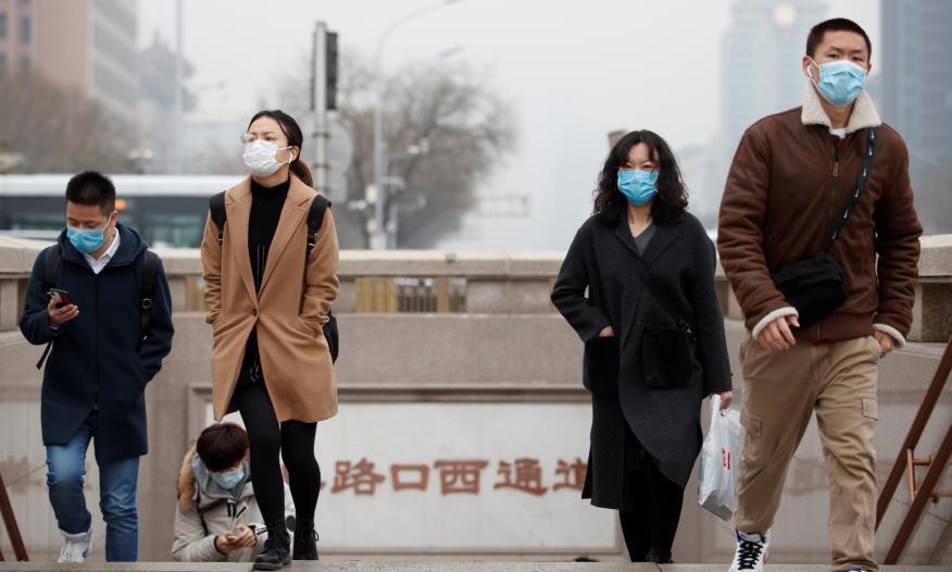 Un grupo de jóvenes con mascarillas salen del metro de Pekín (China)