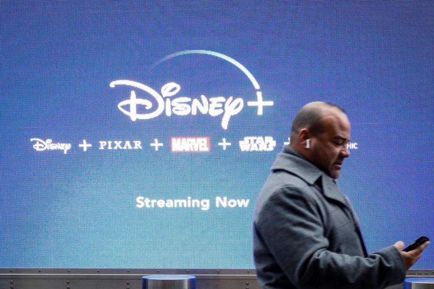 Un hombre pasa por delante de un cartel de Disney Plus