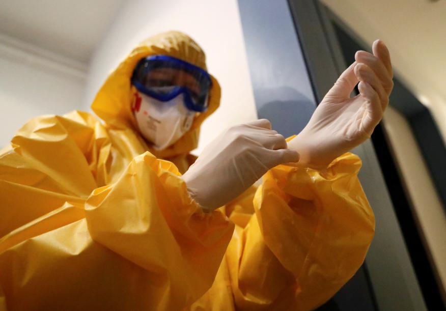 Un médico se equipa con un traje protector en medio de la pandemia del coronavirus