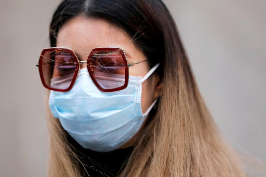 Una mujer con una mascarilla en medio del brote del coronavirus