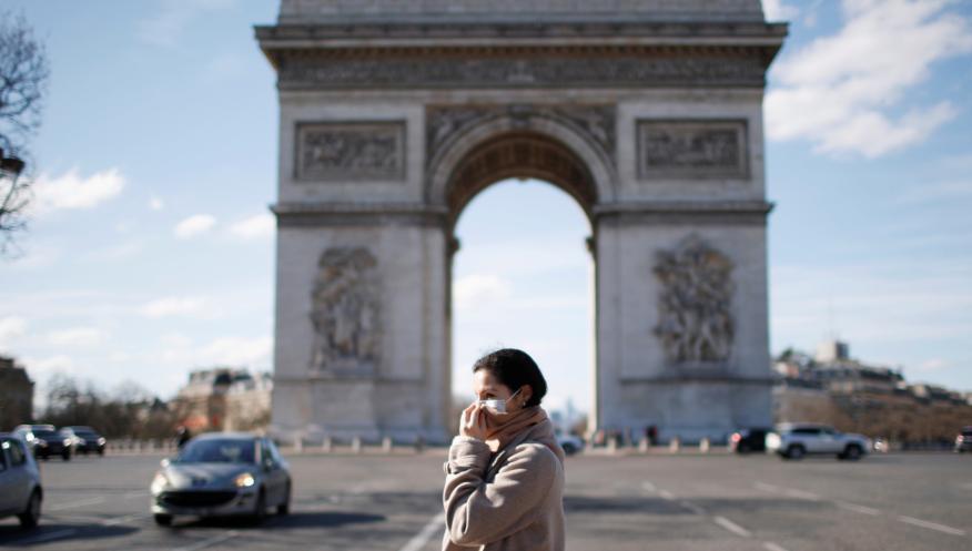 Una mujer con mascarilla pasa ante el Arco del Triunfo de París