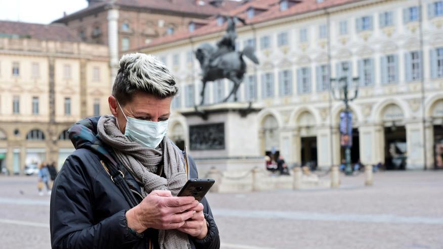 Una mujer mira su móvil durante el brote de coronavirus.
