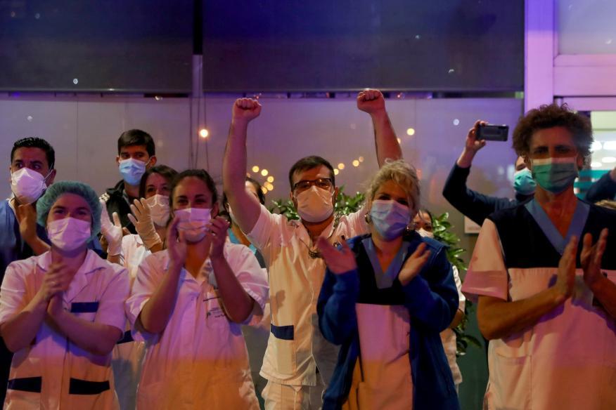 Sanitarios aplauden en las puertas de un hospital.