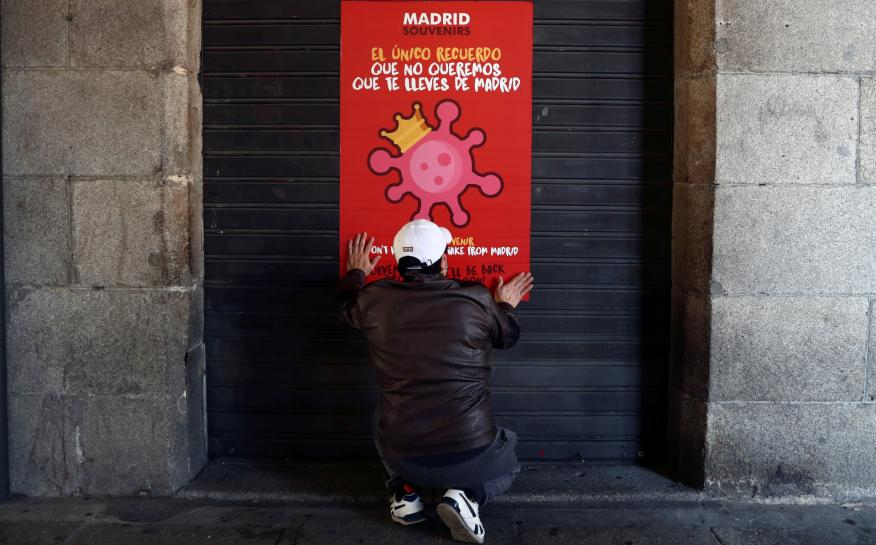 Un trabajador coloca un letrero explicando el cierre de su negocio por el estado de alarma por coronavirus en Madrid