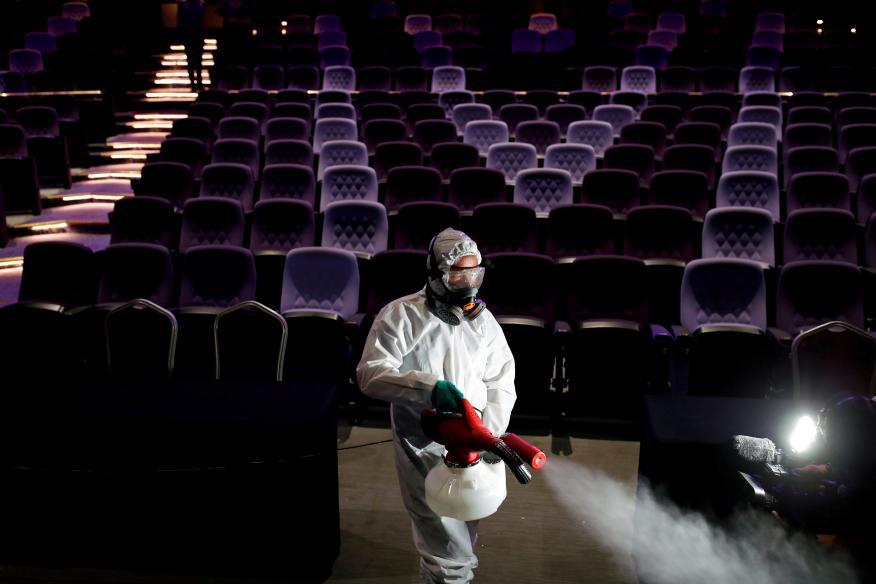 Un trabajador con traje protector desinfecta un teatro en Tailandia en medio del brote del coronavirus
