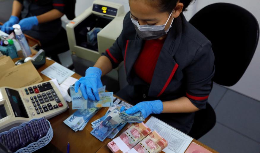 Una trabajadora del Banco Central de Indonesia cuenta billetes antes de su desinfección de coronavirus