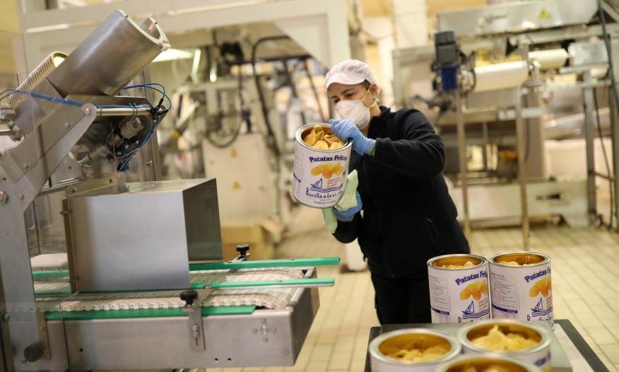 Una trabajadora de Bonilla a la Vista limpia una lata de patatas fritas en la fábrica de la empresa en Arteixo (A Coruña)