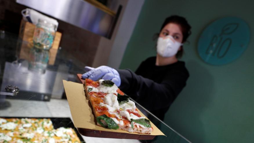 Una trabajadora de una pizzeria de Roma despacha con una mascarilla