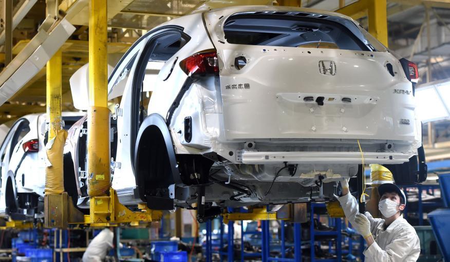 Trabajadores con mascarilla en la fábrica de Honda en Wuhan (China)