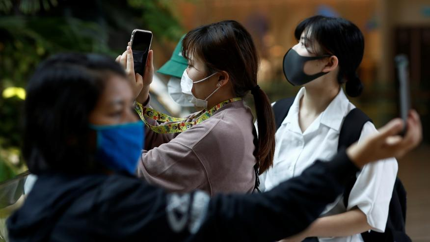 Tres turistas con mascarillas se sacan fotos durante el brote de coronavirus.
