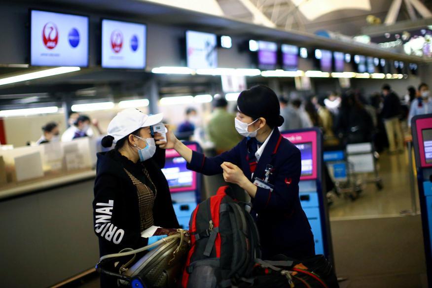 Una empleada de Japan Airlines mide la temperatura de una pasajera en plena pandemia del COVID-19 en el Aeropuerto Internacional de Kansai, en Osaka, Japón.
