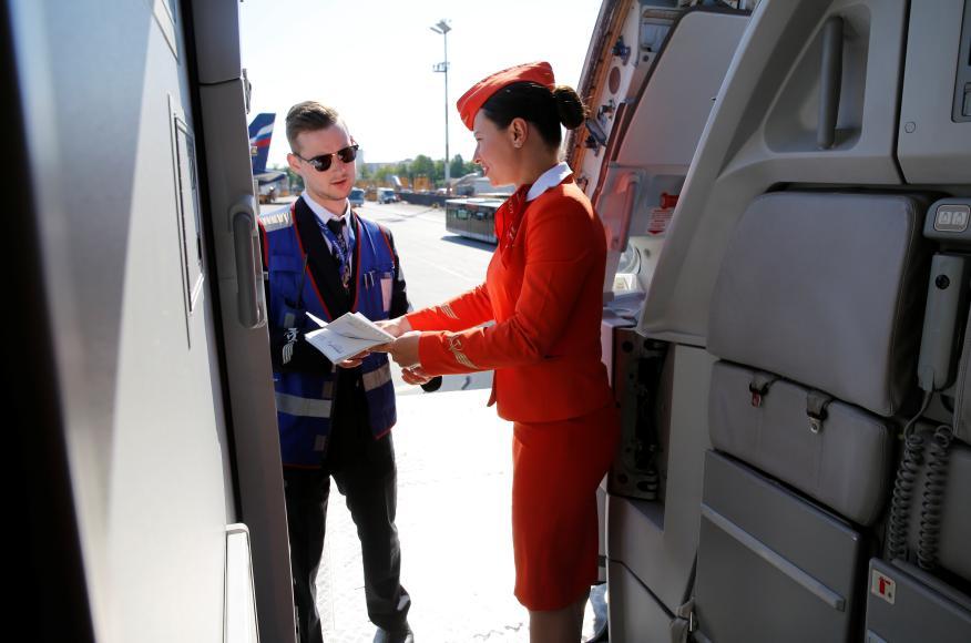 Una tripulante de cabina de pasajeros habla con un trabajador de tierra a las puertas de un avión en el aeropuerto de Sheremetyevo en Moscú, Rusia.