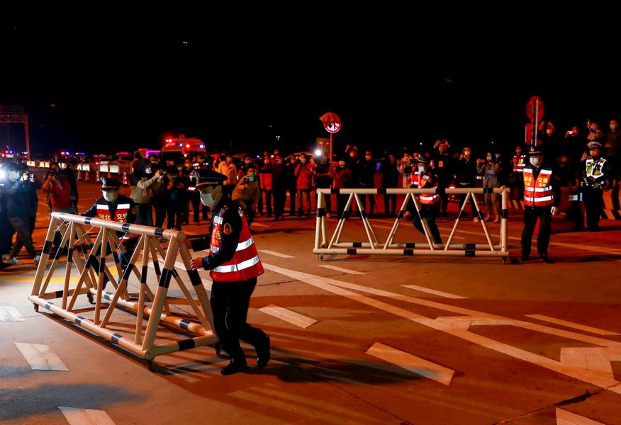 Policías retirando las berraras que aislaban Wuhan.