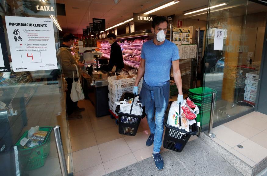Un hombre con mascarilla sale de hacer la compra en la crisis del coronavirus.