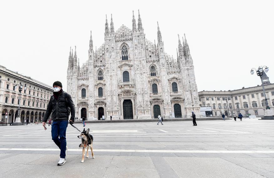 Un hombre pasea a su perro en la plaza del Duomo (Milán) durante la pandemia de coronavirus.