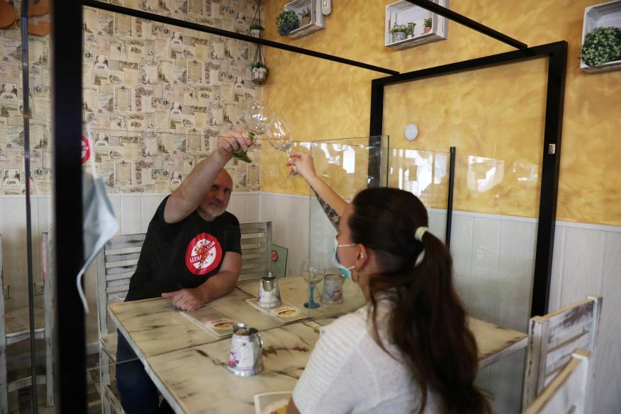 Manuel Gil, fundador de Llenatubar, junto a una empleada en una de las mesas con mamparas de su restaurante en Leganés.