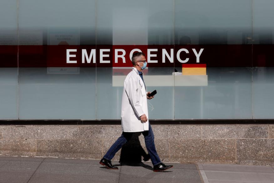 Un medico usa una mascara protectora mientras camina afuera del Hospital Mount Sinai durante el brote de la enfermedad por coronavirus en Nueva York