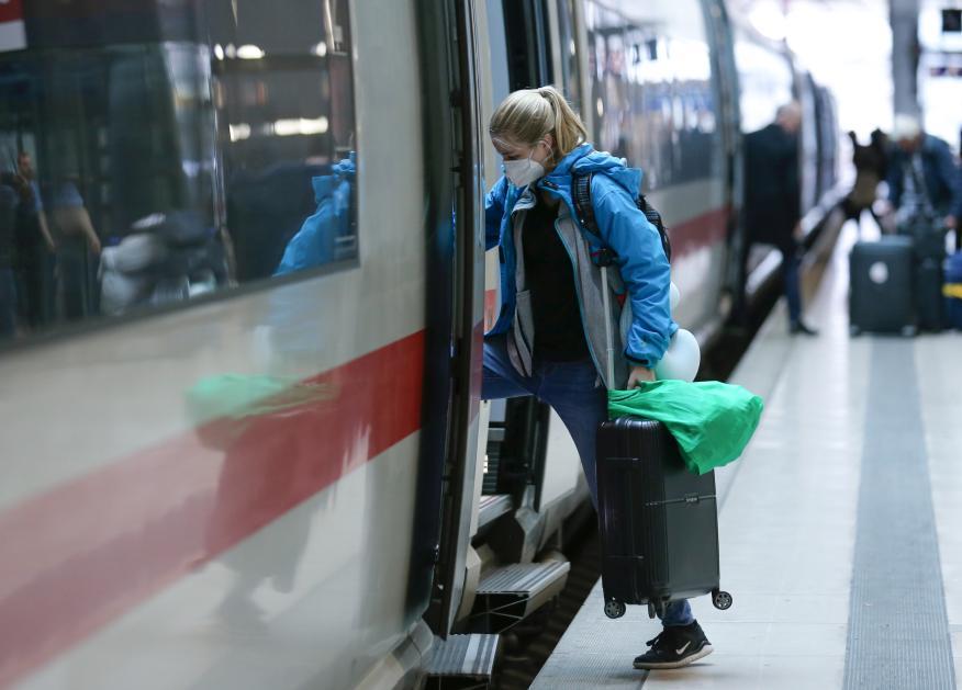 Una mujer sube a un tren en Alemania con mascarilla por el coronavirus.