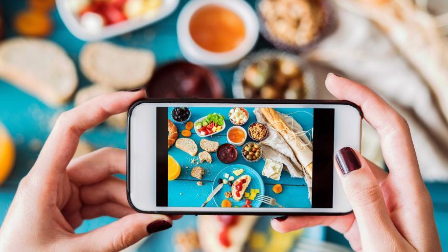 Una mujer toma una foto de comida.