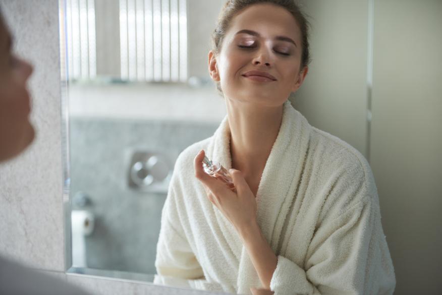 Una mujer utilizando un perfume.