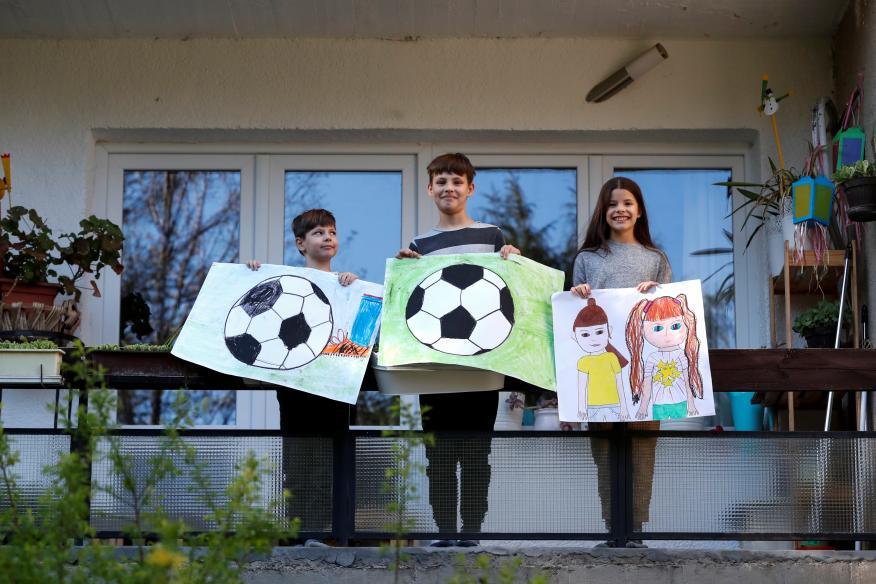 Unos niños muestran dibujos pintados durante el confinamiento por el coronavirus