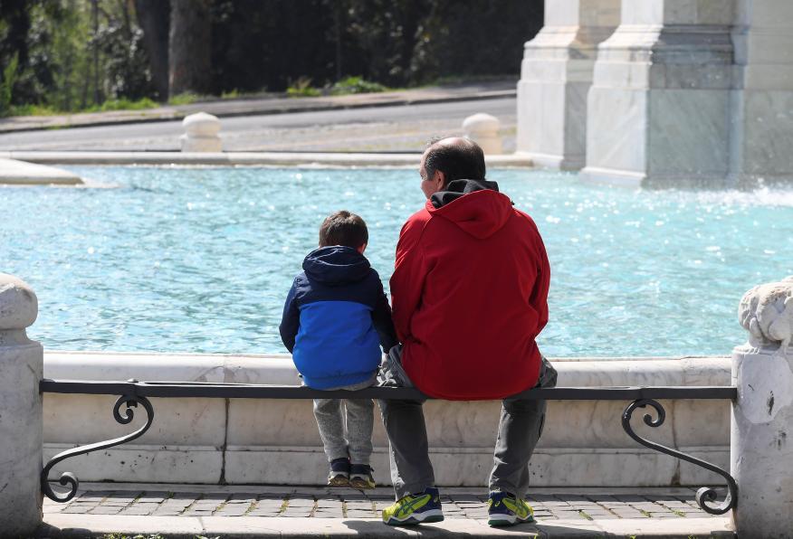 Un padre y un hijo sentados mirando una fuente.