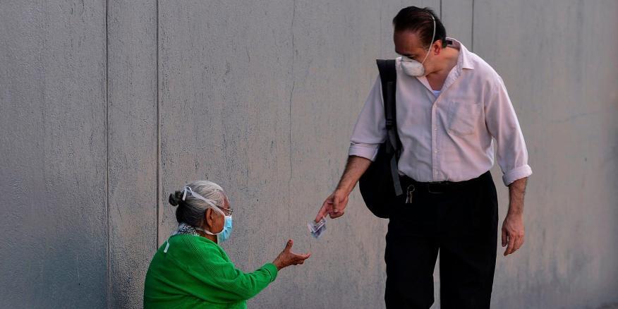 Un transeúnte da dinero a una mujer sin hogar en Honduras.