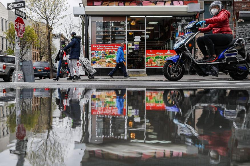 Pedestrians and motorists wear personal protective equipment as they pass a small grocery that is one of the few businesses open on the street in New York. (AP Photo/John Minchillo)