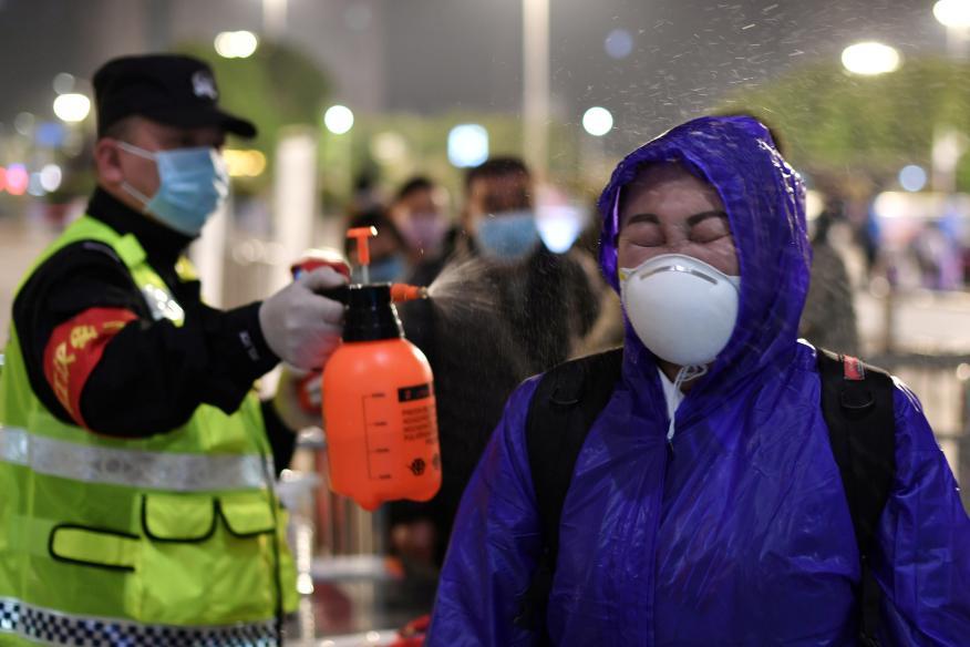 Un policía rocía con desinfectante a un viajero en la estación de trenes de Wuhan