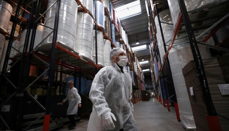Trabajadores con mascarilla y equipos de protección en una fábrica en Anjou (Francia)