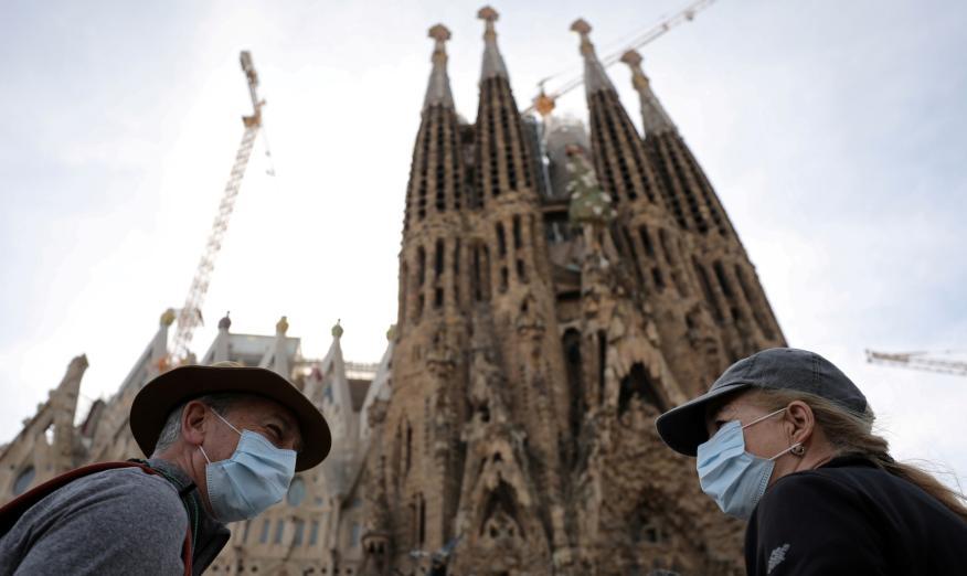 Turistas con mascarilla ante la Sagrada Familia de Barcelona