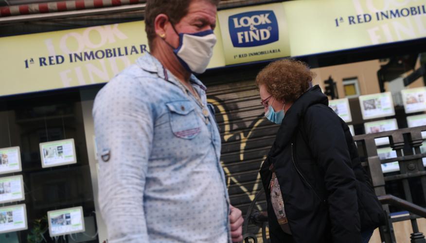 Dos viandantes con mascarilla pasan ante una inmobiliaria en Madrid