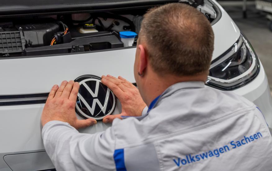Un empleado coloca una placa de VW en una línea de producción en la planta de Zwickau.