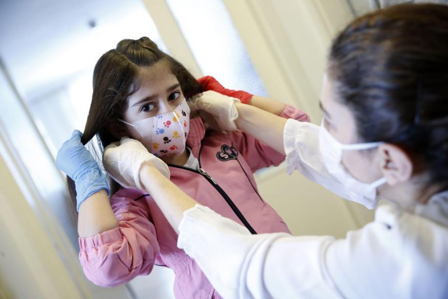 Una niña usa guantes y una mascarilla antes de ir al parque, después de que se permitiera a los niños menores de 14 años salir de sus casas en Turquía, el 13 de mayo de 2020.