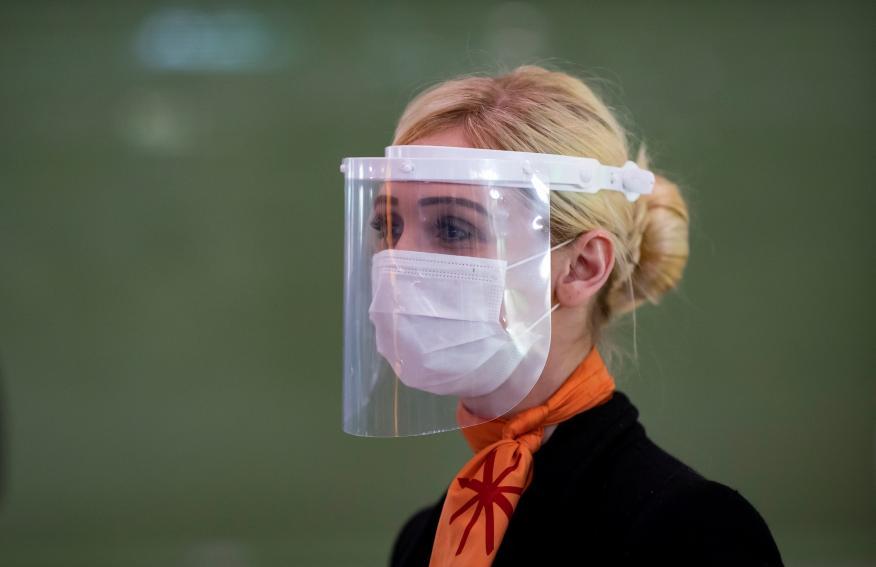 Una mujer se protege con una pantalla facial en un aeropuerto en medio de la pandemia del coronavirus