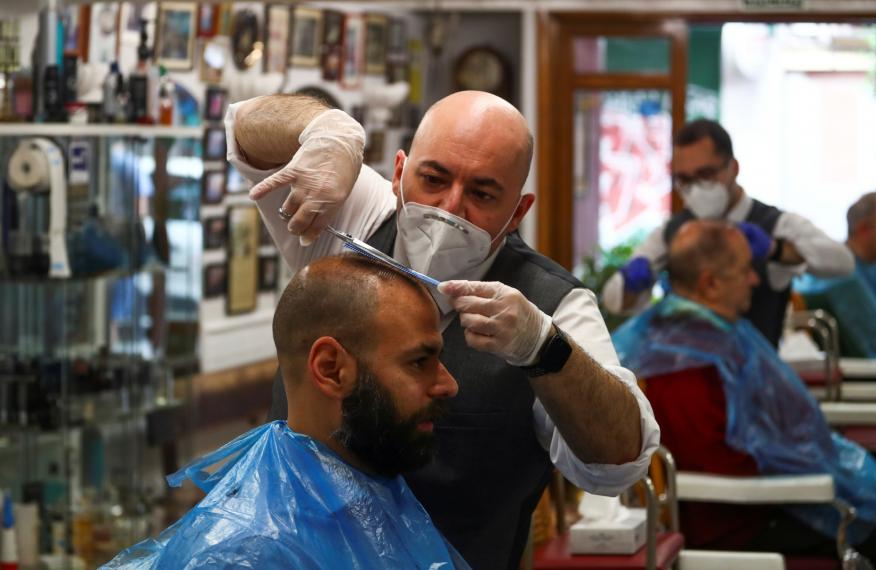 Un peluquero en su peluquería en la desescalada del coronavirus en España