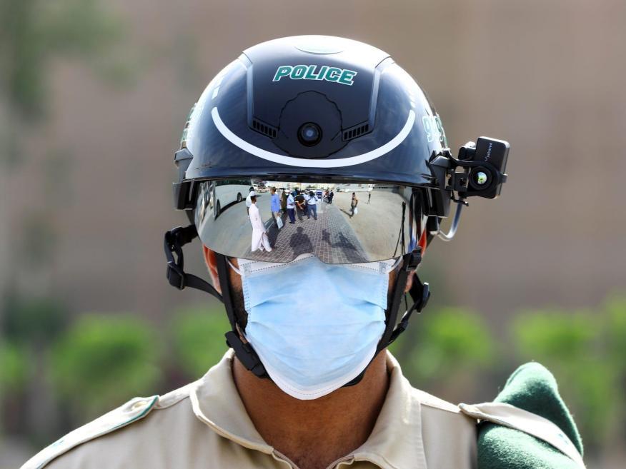 Un oficial de policía lleva un casco inteligente mientras lo usa para comprobar la temperatura de los trabajadores, durante el brote de la enfermedad coronavirus (COVID-19) en Dubái