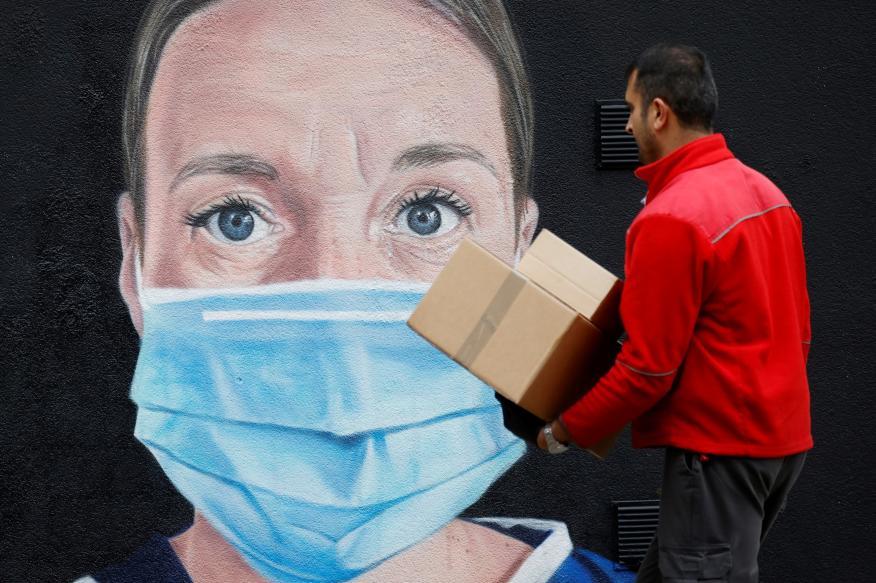 Un repartido pasa por delante de un mural con motivo de la pandemia del coronavirus