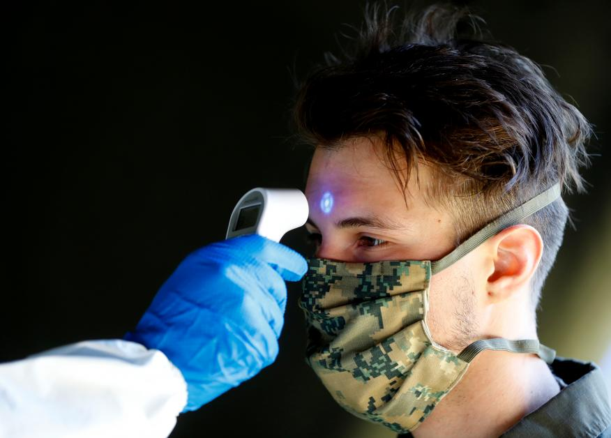 Un soldado del ejército austriaco toma la temperatura a un compañero durante la crisis del coronavirus en Viena