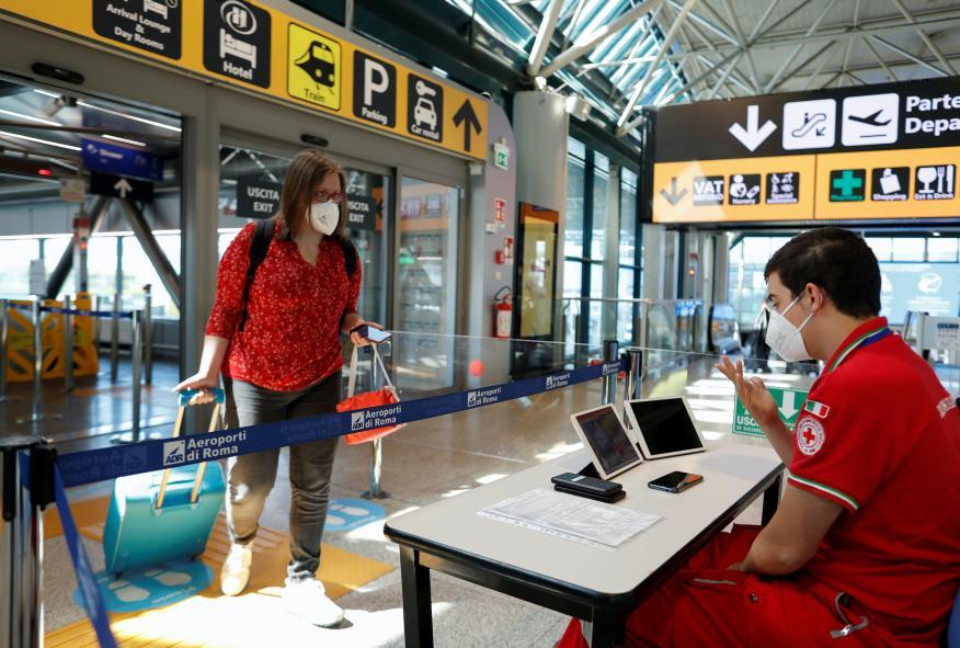 Una pasajera y un miembro de la Cruz Roja italiana en el Aeropuerto de Fuimicino, en Italia.