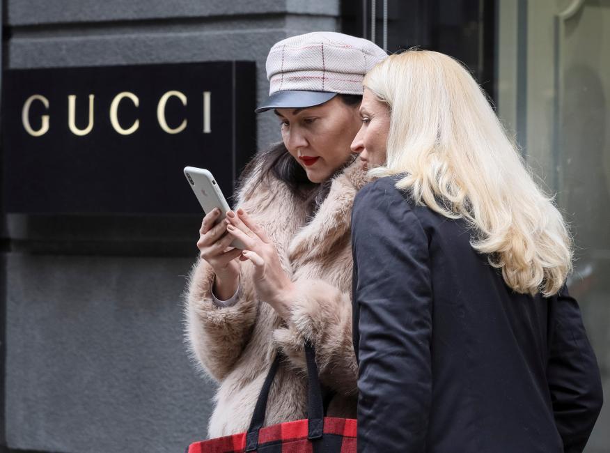 Dos mujeres miran un móvil frente a un escaparate de Gucci