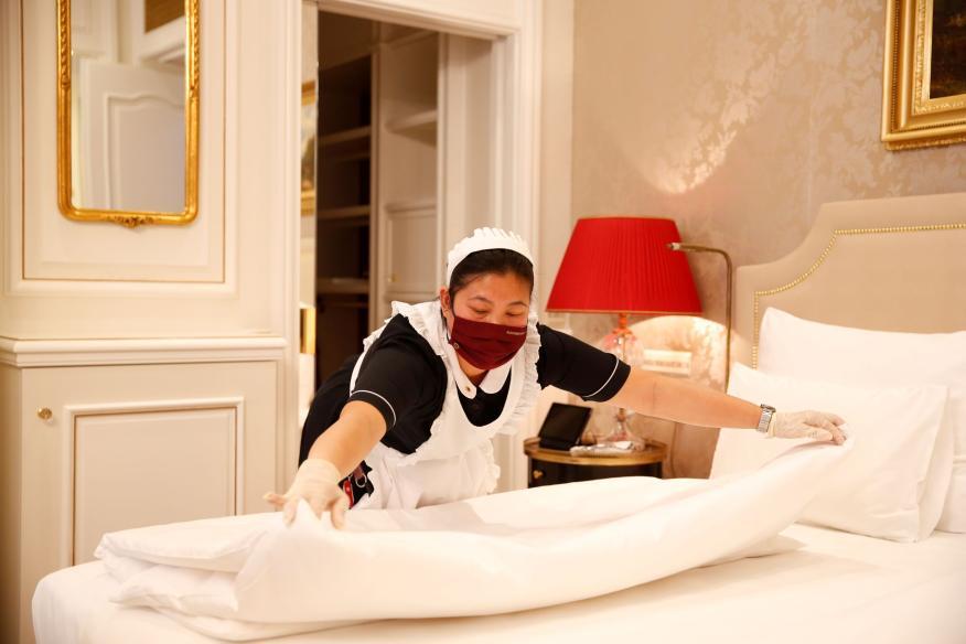 Una empleada de la limpieza con mascarilla arregla la habitación de un hotel en Viena, Austria.