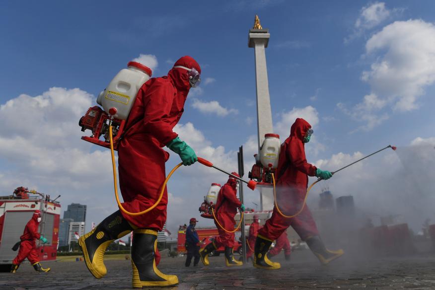 Un grupo de bomberos con trajes protectores desinfecta una zona turística en Yakarta pare frenar la propagación del coronavirus.