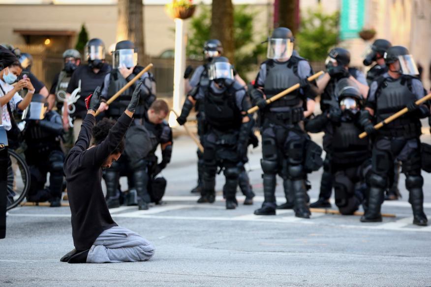 Un manifestante se arrodilla ante los antidisturbios durante las protestas en Georgia por la muerte de George Floyd
