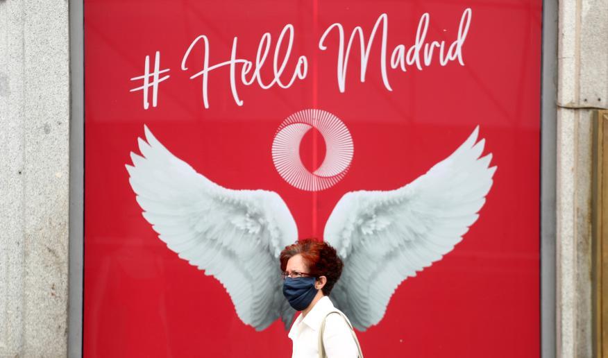 Una mujer con mascarilla pasa ante un anuncio en una zona turística de Madrid