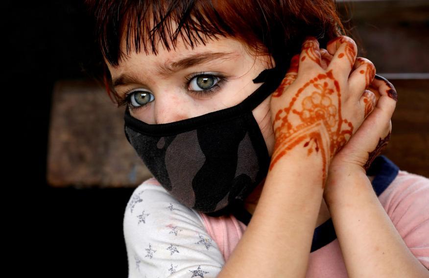 Una niña se ajusta una mascarilla en medio de la pandemia del coronavirus en Pakistán