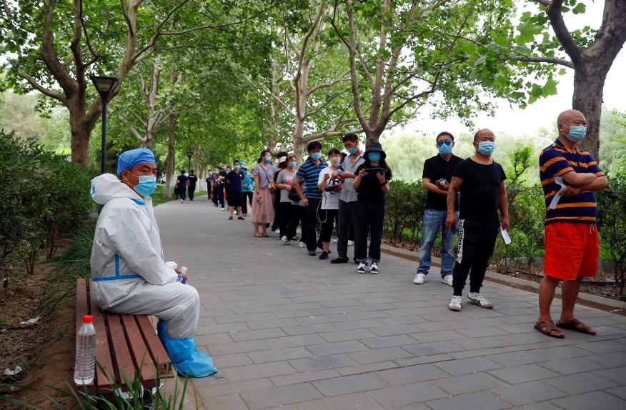 Residentes de Pekín hacen fila para hacerse una prueba de ácido nucleico en un parque en el distrito de Fengtai.