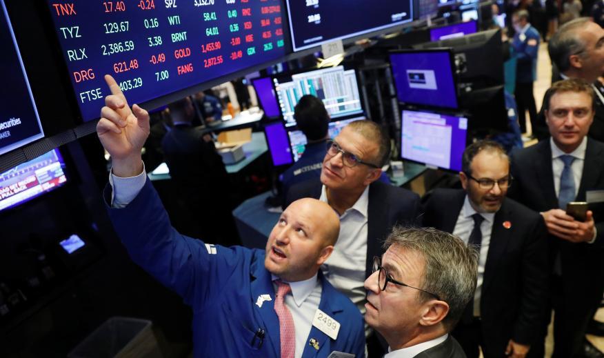Traders observan las cotizaciones en Wall Street.